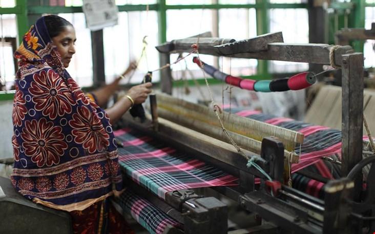 Een vrouw weeft stoffen voor het fair trade merk People Tree
