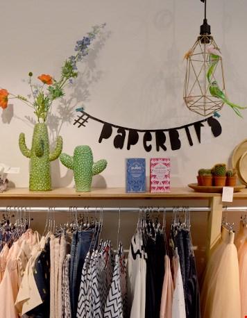 Inspiratieplanken boven de kledingrekken